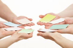 Human hands reaching out colorful paper cards Royalty Free Stock Images