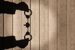 Human Hands Shadow with Handcuffs on Natural Wooden Backround, X Royalty Free Stock Photo