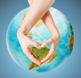 Human hands showing heart shape over earth globe. People, peace, love, life and environmental concept - close up of human hands showing heart shape gesture over stock image
