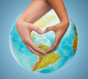 Human hands showing heart shape over earth globe. People, peace, love, life and environmental concept - close up of human hands showing heart shape gesture over royalty free stock photos