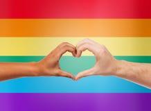 Human hands showing heart shape over rainbow stock photo