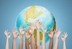 Human hands showing ok sign over earth globe. Gesture, people, humanity and community concept - human hands showing ok sign over earth globe and blue background Royalty Free Stock Image