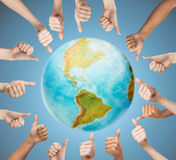 Human hands showing thumbs up in circle over earth Stock Images