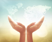 Human hands sign. Human open two empty hands with palms up on world map of clouds background stock photo