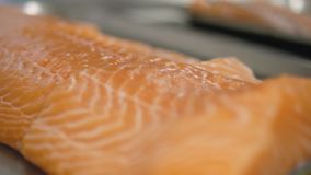 Human hands take a piece of sliced salmon fillet close-up. stock video footage