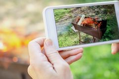 Human hands is taking pictures of the fire on smartphone. Outdoo. Rs. Close-up Royalty Free Stock Images