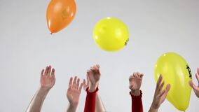 Human hands throw up balloons with symbols of cryptocurrency.