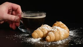 Human hands to break with coffee and croissant on black background.  stock video