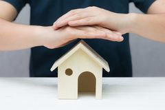 Human hands try to protect wooden toy house. Home model. Property insurance and security concept Stock Image