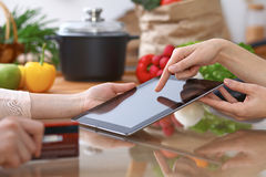 Human hands of two female persons using touchpad in the kitchen. Closeup of two women are making online shopping by Royalty Free Stock Image