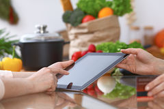 Human hands of two female persons using touchpad in the kitchen. Closeup of two women are making online shopping by Royalty Free Stock Photos