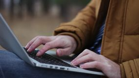 Human hands typing text on laptop keyboard in park on bench.  stock footage