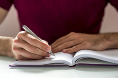 Human Hands Writing on Notebook on Top of Table Stock Photos