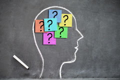 Human head shape drawn on a blackboard with question marks on post-its inside Stock Photography