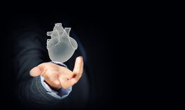 Human heart. Close up of businessman holding human heart in palm stock photography