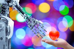 Human heart on hand send to an artificial robot in Valentine day for make the robots have love like a human stock photos