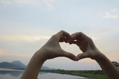 Human heart in the sky background. Hand Stock Photos