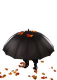 Human hiding under umbrella Stock Photo