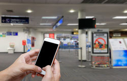 Human holding blank screen of smart phone and waiting departures royalty free stock image