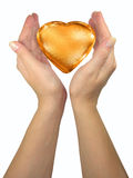 Human lady hands holding golden heart. Isolated over white background royalty free stock photos