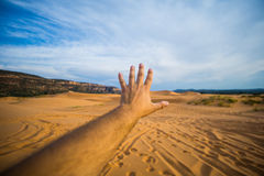 Human Left Hand over Brown Sand at Desert over White and Blue Sky during Daytime Royalty Free Stock Photography