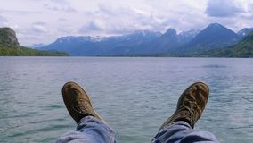 Human Legs on the Background of a Mountain Lake and Snow-covered Mountains. Concept of success, goal achievement, freedom, relaxation. Traveler sits on a pier stock footage