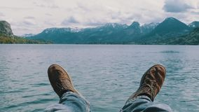 Human legs on the background of a mountain lake and snow-covered mountains. Concept of success, goal achievement, freedom, relaxation. Traveler sits on a pier stock video