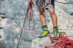 Human legs on cliff with rope. Royalty Free Stock Images