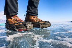 Human legs in hiking boot in ice crampons on the texture Baikal Royalty Free Stock Photography