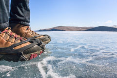 Human legs in hiking boot in ice crampons on the texture Baikal Stock Photo