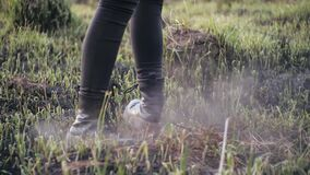 Human legs in stylish leather shoes spin in a circle on ashen burnt grass in slow motion in sunny weather. Person is
