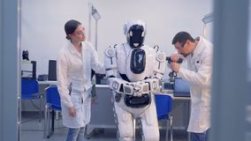Human-like cyborg is getting checked and fixed by two engineers. 4K stock footage