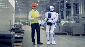 Human-like cyborg is getting switched on and set up by a male factory worker stock video footage