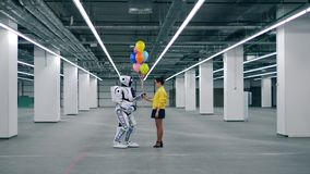 Human-like cyborg and a woman are holding balloons stock video footage