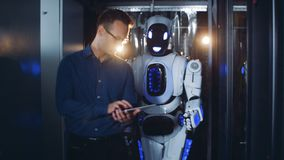 Human-like droid is being guided by a walking male expert