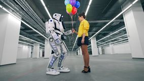 Human-like robot and a girl are holding balloons together stock video