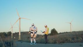 A human-like robot and a male operator are walking along the set of windmills. 4K stock video