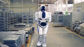 A human-like robot is putting a piece of fitting and walking away in a factory warehouse. A human-like robot is putting a piece of fitting and walking away. 4K stock video footage