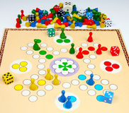 Human ludo. Ludo, playing figures and dice on game board Royalty Free Stock Photos