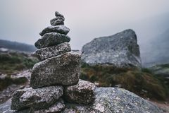 Human-made pile of stones - cairn as way marker in foggy mountai Stock Images