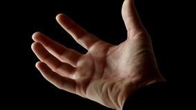 Male palm is clenched into a fist. Human male palm in the rays of light isolated on black background. A man shows an open hand, then slowly clench his fingers stock video footage