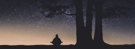 Human meditate under the big tree. Instagram stylization. Human meditate in a lotus pose under the big tree against starry night sky. Instagram stylization stock image