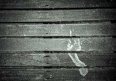Human mud footprint on dark wooden plank floor with space. Human mud footprint on dark wooden plank floor with copy space Stock Image