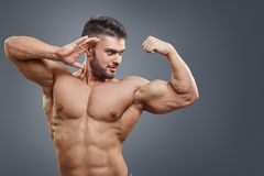 Human Muscle Bicep Growth concept. Strong man surprised of his muscular arm isolated on grey background Royalty Free Stock Image