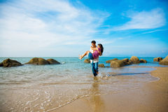 Human and nature. Loving couple of the guy carrying the woman walking along the beach Stock Photography