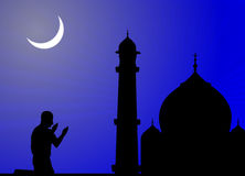 Human offering prayers, mosque. Silhouette of human offering prayers at mosque and crescent shaped moon Stock Photo