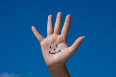 Human palm with smile Stock Photos
