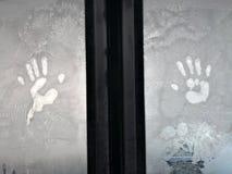 Human palms on frosty window. Close up shot of a human palms imprint on a frosty window stock photos
