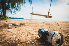 Cans on the beach destroy the environment. Garbage in the sand on nature. trash on on a beautiful beach with a swing stock photography