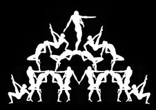 Human Pyramid in Black. White silhouettes against a black background of women working together to form a human pyramid Stock Photography